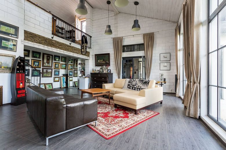 гостиная с белой кирпичной стеной и галереей