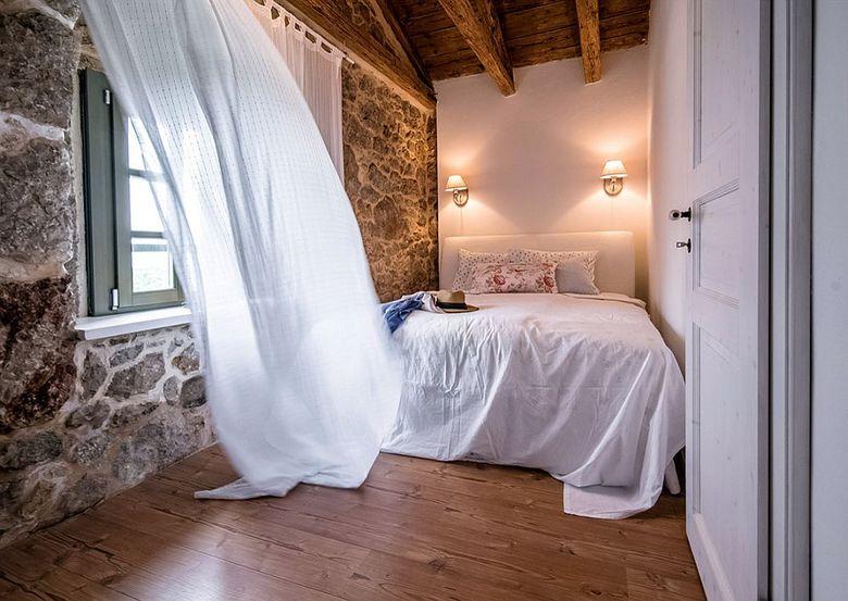 Каменная стена и деревянный потолок в спальне