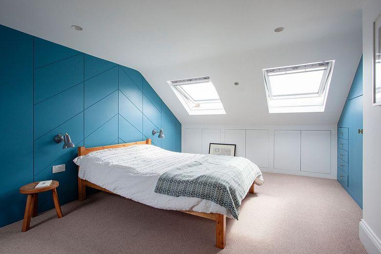Белая спальня с синими шкафами и яркой акцентной стеной