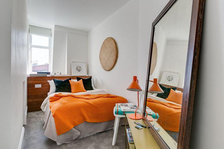 Белая спальня с большим зеркалом на полу и желтыми вставками
