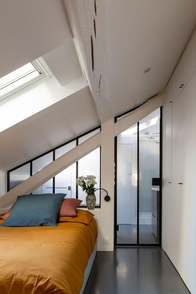 Белая спальня с мансардными окнами серым полом